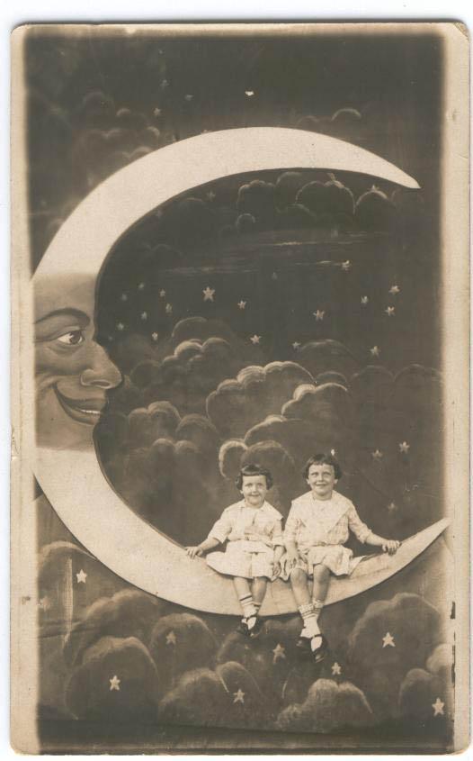 Two small girls in dresses on moon swing paper moon cardboard sky stars dark clouds night nighttime